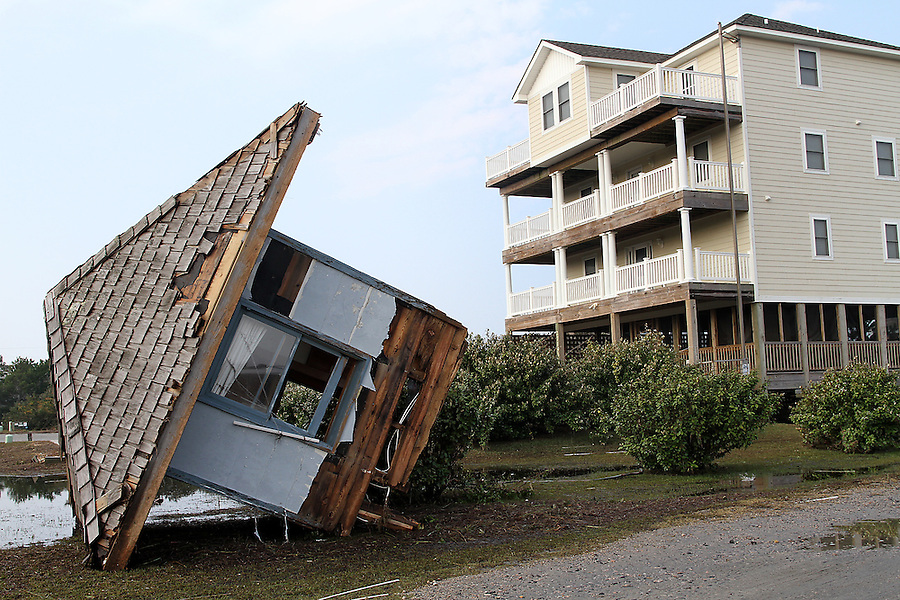 The top of the 100-year-old Pea Island Life Saving Station, which had been on display at ground level at Hatteras Watersports in Salvo, NC, got washed up near a much more modern structure by floodwaters from Hurricane Irene, seen on Monday, Aug. 29, 2011.  Photo by Ted Richardson