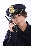 A young woman police officer listening to the radio communication