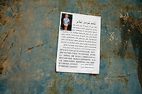 A missing persons poster hangs on a wall in Kashgar, Xinjiang, China.  When authorities arrest Uighurs, they often disappear without a trace.