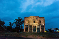 Old abandoned brick building at night in Duran, New Mexico