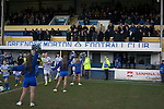 Home team players running out onto the pitch past young majorettes before Greenock Morton take on Stranraer in a Scottish League One match at Cappielow Park, Greenock. The match was between the top two teams in Scotland's third tier, with Morton winning by two goals to nil. The attendance was 1,921, above average for Morton's games during the 2014-15 season so far.