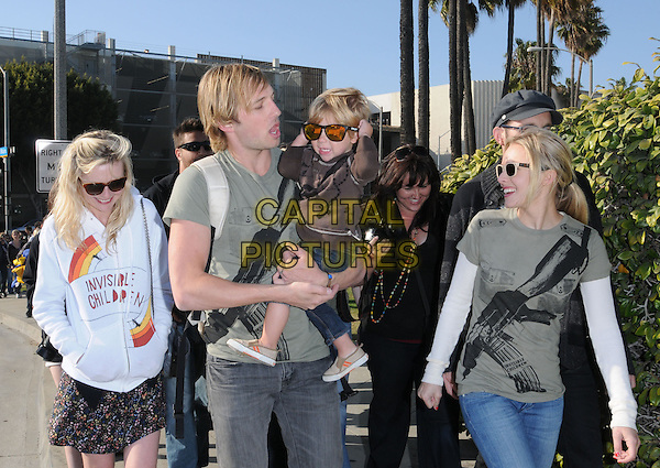 "RYAN HANSEN, KIRSTEN DUNST & KRISTEN BELL.City Hall at The Invisible Children's ""THE RESCUE"" Rally at City Hall in Santa Monica, California, USA, .half length green gun print t-shirt white top ray bans wayfarers sunglasses cream two tone hoodie carrying child kid boy.CAP/DVS.©DVS/RockinExposures/Capital Pictures"