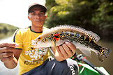 BRAZIL, Agua Boa, fishing guide holding a fish, Agua Boa River and resort