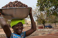 Woman carrying shea nuts for processing into butter