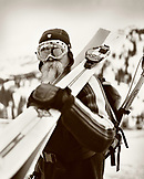 USA, Utah, male telemark skier carrying skis on his shoulder (B&W)