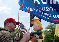 """Christopher Casey, of Brooklyn, New York, exchanged words with people who turned out to view the """"Baby Trump"""" blimp and the Trump Tweeting statue in Washington D.C. on July 4, 2019. Photo Credit: Stefani Reynolds/CNP/AdMedia"""