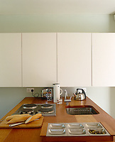 In this minimal kitchen a row of plain white painted cupboards is bisected by the Douglas Fir work surface of a kitchen island containing an integral hob and stainless steel sink