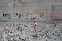 People walk among stone formations built by others from stones found on a reef under a bridge emerging from the water because of the low water level of River Danube in central Budapest, Hungary on Aug. 22, 2018. ATTILA VOLGYI