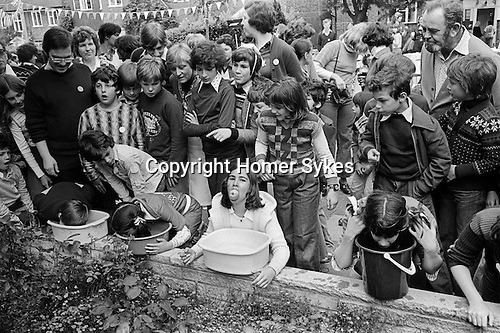 Silver Jubilee Street Party 1977 Hampstead Garden suburb. Children playing in a Apple Dunking or Apple Bobbing or Bobbing for Apples  competition.<br />