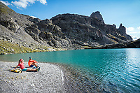 Two people sit relaxing on the shore of the Schottensee, during a trail run below the Pizol, Switzerland