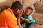 Baby boy 10 months old at home playing peek a boo with father