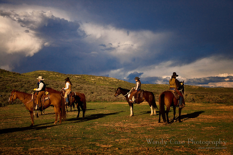 Cowboys and cowgirls on horseback watching stormcloud formation, Colorado.
