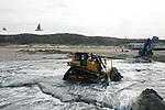 Foto: VidiPhoto<br /> <br /> DOMBURG – In opdracht van Rijkswaterstaat wordt voor het begin van het toeristenseizoen hard gewerkt aan het ophogen van het strand bij Domburg. Tot mei wordt er in totaal 500.000 kubieke meter zand over een lengte van 1800 meter vanuit de zee op het strand gespoten. Het gaat om het vierjaarlijks onderhoud. Het strand is in fases afgesloten. Alleen het werkgebied waar wordt opgespoten, of waar machines rijden, is niet toegankelijk voor andere gasten. Het opspuiten gebeurt via een zandzuiger op zee. Een baggerschip pompt vlak voor de kust het zand via een lange pijpleiding naar het strand. Bulldozers verdelen dit zand over het strand. Elke vier jaar stelt Rijkswaterstaat een plan op voor het onderhoud aan de Nederlandse kust. Om te bepalen waar onderhoud nodig is, wordt eerst de ligging van de kust gemeten. Het extra zand wordt volgens Rijkswaterstaat ook gestort om de zeespiegelstijging bij te blijven. Kennisinstituut Deltares verwacht dat door een versnelde stijging van de zeespiegel vanaf 2050 er meer en grotere zandsuppleties langs de gehele Nederlandse kust nodig zijn.