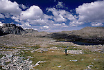 A lone backbacker crosses a high plateau in the Wind River Range of Wyoming.
