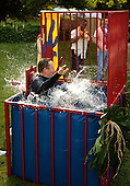 Washington, DC - June 25, 2009 -- White House Press Secretary Robert Gibbs falls into a water dunk tank after members of the news media threw balls at the target before a luau for members of Congress and their families on the South Lawn of the White House June 25, 2009 in Washington, DC. In a celebration of U.S. President Barak Obama's home state, the South Lawn was decorated with tiki torches and palm huts and the meal prepared by famous Hawaiian chef Alan Wong. .Credit: Chip Somodevilla - Pool via CNP