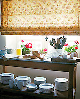 Fresh bread and cheese laid out on a marble-topped wooden trolley infront of a sunny windowsill