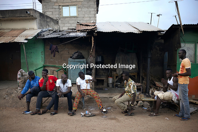 ACCRA, GHANA APRIL 18: Daily life in a street in Zongo area on April 18, 2015 in Accra, Ghana. Many young unemployed men here are involved in Romance scams, credit card fraud and etc. The country is a center for different online scams. Both men and women are lured to send cash to someone they only met on the net.  Due to limited opportunities, many youngsters spend their days in Internet cafes trying to scam people form all over the world. (Photo by: Per-Anders Pettersson)