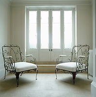 An elegant seating area with upholstered garden chairs has been created on a small landing off the main staircase