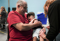 NWA Democrat-Gazette/CHARLIE KAIJO Mike Henzie of Bella Vista (left) holds Brooks Henzie, 1, as Amber Carter APRN (right) gives him a flu shot during a free flu vaccine clinic, Friday, October 5, 2018 at the Rogers Community Center in Rogers.<br /><br />The Benton County Health Unit of the Arkansas Department of Health (ADH) will offer free flu vaccinations at the Rogers Activity Center, 315 W. Olive, Rogers, AR., from 8:00 a.m. to 4:00 p.m. Friday. <br /><br />&Ograve;We want Benton County residents to stay healthy this flu season, and getting a yearly flu vaccination is the best line of defense,&Oacute; Loy Bailey, Benton County Health Unit Administrator, said. &Ograve;We encourage everyone to come to the mass clinic or the local health unit to get their flu shot.&Oacute;