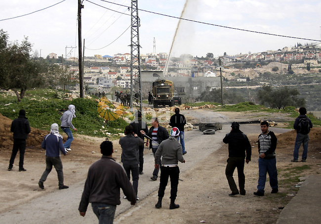 Palestinian protesters throw stones at Israeli soldiers during a demonstration against the expropriation of Palestinian land by Israel in the village of Kfar Qaddum, near the West Bank city of Nablus, on February 24, 2012.  Photo by Wagdi Eshtayah