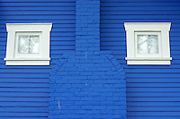 White windows on a blue wooden wall of a house in Kitsilano, a Greek neighborhood of Vancouver, British Columbia, Canada