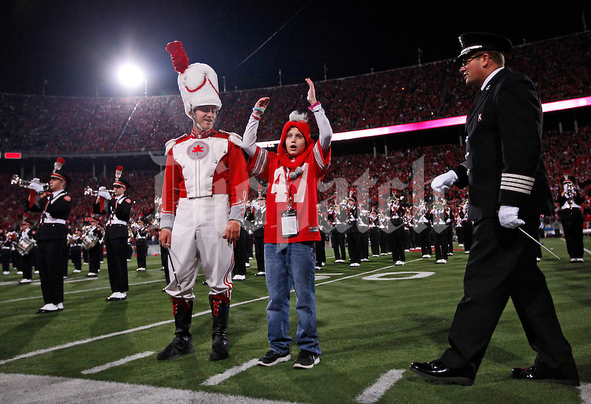 "With drum major Kyle West and director Jon Waters at his side, cancer survivor Grant Reed leads the Ohio State Marching Band and Ohio Stadium in a round of the O-H, I-O chant prior to the NCAA football game against Penn State in Columbus on Oct. 26, 2013. Reed named his cancer ""Michigan"" and vowed to beat it while in the hospital this past year. His parents were members of the band when they were in college. (Adam Cairns / The Columbus Dispatch)"
