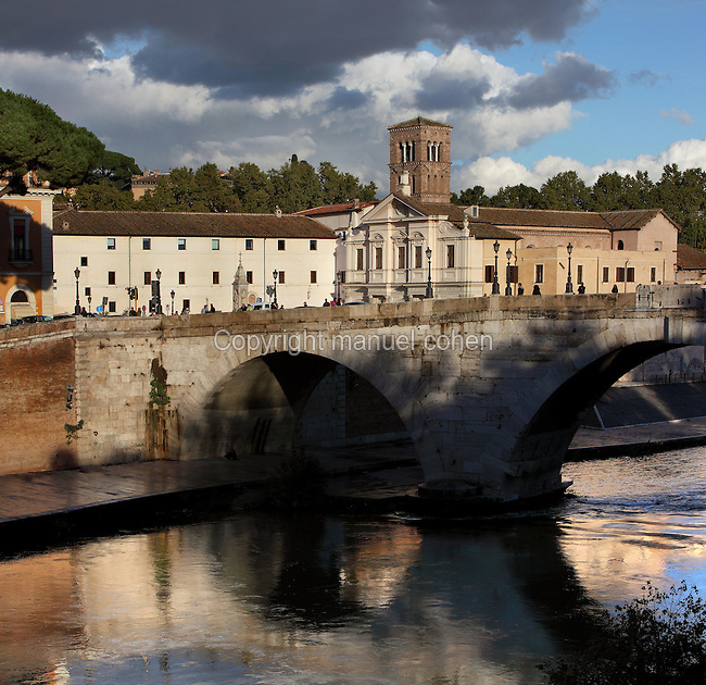 Ponte Cestio (1st century BC, rebuilt 19th century) over River Tiber to Isola Tiberina, Rome, Italy. Dramatic view of the bridge in the shade of the trees and beneath a stormy sky. Photograph by Manuel Cohen.