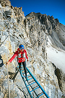 Descending ladders and cables on the Schöllijoch during the Via Valais, a multi-day trail running tour connecting Verbier with Zermatt, Switzerland.
