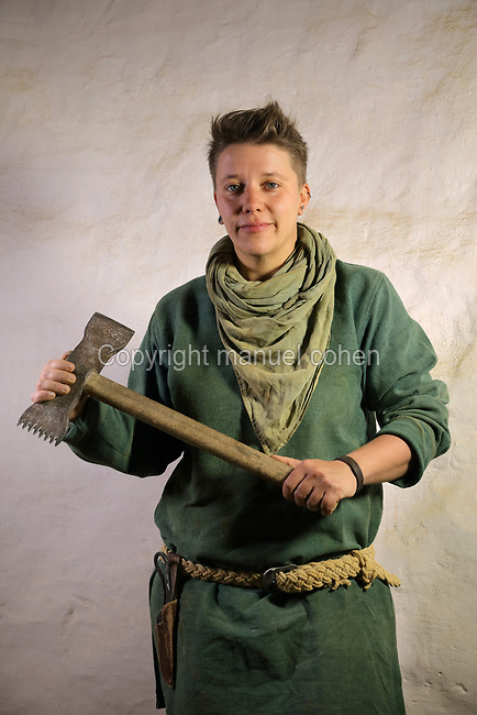 Aline Meunier, stone cutter on the Guedelon project since 01/08/2014, wearing medieval costume and holding a tooth axe, at the Chateau de Guedelon, a castle built since 1997 using only medieval materials and processes, in Treigny, Yonne, Burgundy, France. The Guedelon project was begun in 1997 by Michel Guyot, owner of the nearby Chateau de Saint-Fargeau, with architect Jacques Moulin. It is an educational and scientific project with the aim of understanding medieval building techniques and the chateau should be completed in the 2020s. Picture by Manuel Cohen