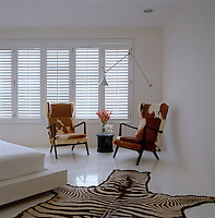 A pair of wing-back armchairs upholstered in cowhide and a zebra-skin rug furnish the otherwise all white master bedroom
