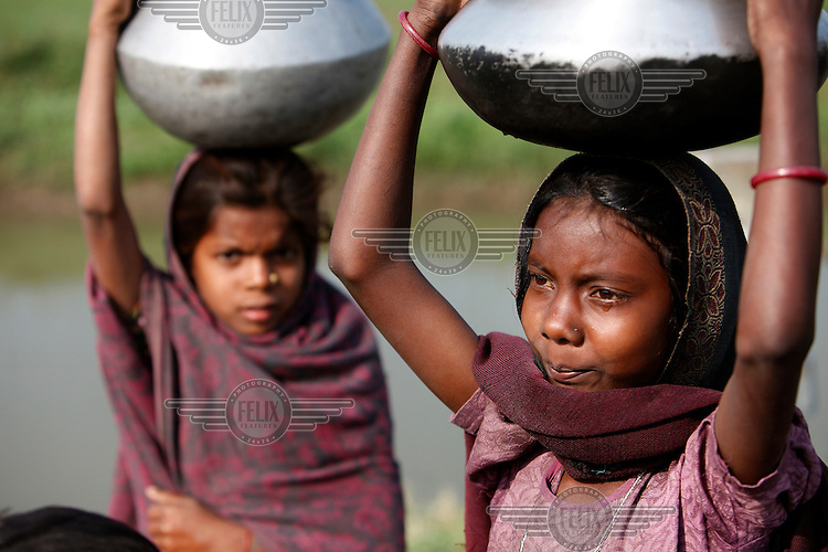 Two young girls carry metal jugs full of water back home from a communal pump.