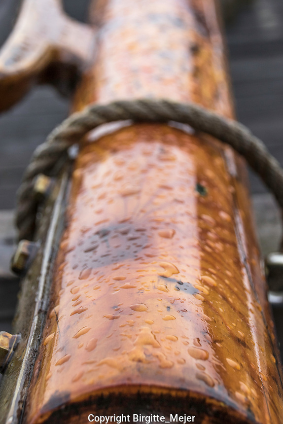 wooden mast for a sailboat taken off for the winter, with the winter raindrops on it. Up close photography