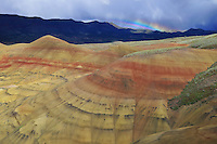 Small rainbow briefly forms behind a section of Painted Hills National Monument in central Oregon.