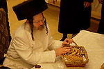 Israel, Bnei Brak. Purim feast at the Premishlan congregation, the Rabbi tastes the Purim gifts. His White robe used rarely, on holidays like Yom Kippur, Purim and weddings of his children, 2005<br />