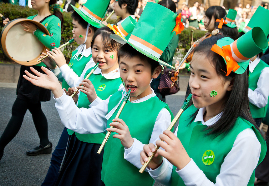 School kids dressed in green playing flute during Tokyo`s St.Patrick`s day parade.