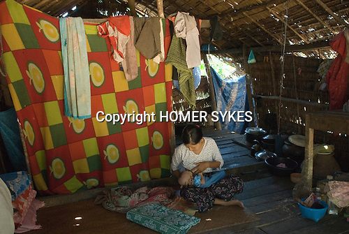 Ngwe Saung interior of a typical village home. Mother breast feeding new born baby. Burma Myanmar. 2011.
