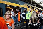 Amsterdam, 30 april 2011.Koninginnedag op en rond Amsterdam Centraal Station; een NS medewerker geeft aanwijzigen temidden van terugkerende feestvierders..Foto Felix Kalkman