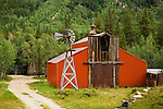 Red metal barn with wooden façade, cupola with weather vane with a metal Dempster windmill on wooden tower in the forest of Colorado's Rocky Mountains.