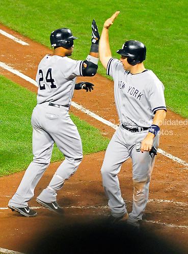 New York Yankees second baseman Robinson Cano (24) is  congratulated by first baseman Mark Teixeira (25) after Cano homered in the sixth inning against the Baltimore Orioles at Oriole Park at Camden Yards in Baltimore, Maryland in the second game of a doubleheader on Sunday, August 28, 2011.  The Yankees won the game 8 - 3, earning a split in the two games..Credit: Ron Sachs / CNP.(RESTRICTION: NO New York or New Jersey Newspapers or newspapers within a 75 mile radius of New York City)