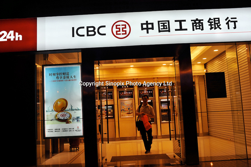 People withdraw money from ATM machines at Industrial & Commercial Bank of China in Guangzhou, China...