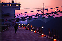 Iron ore is unloaded via a self unloading conveyor at sunrise aboard the lake freighter M V Indiana Harbor, operated by American Steamship Company and GATX. CSA-5854.
