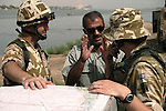 An Iraqi civil engineer talks about an irrigation project to two British Army Royal Engineers responsible for overseeing the use of coalition funds.