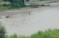 01-AUG-02: NORTH KOREAN BORDER: TUMEN, JILIN, CHINA<br /> A man swims in the Tumen river on the banks of the  North Korea border town of Nanyang. North Korean refugees are reported to be crossing in this area to scavenge for food in China despite a massive security crack-down in the area.