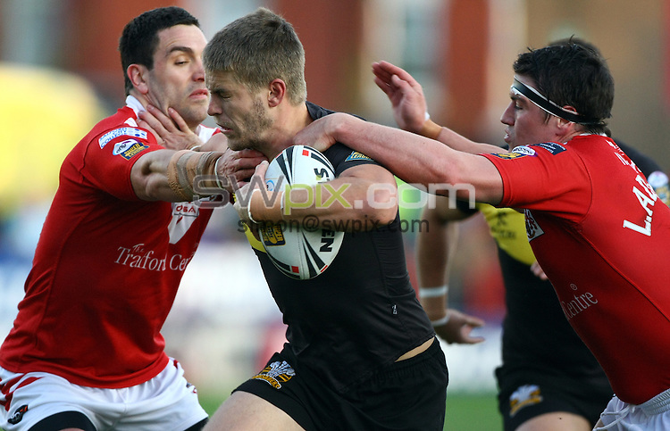 PICTURE BY VAUGHN RIDLEY/SWPIX.COM...Rugby League - Super League - Salford City Reds v Crusaders RL - The Willows, Salford, England - 02/04/11...Salford's Stephen Wild and Luke Adamson tackle Crusaders Rhys Hanbury.