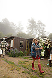 USA, California, Big Sur, Esalen, Kat carries flowers in front of the tool shed in the Buddha garden