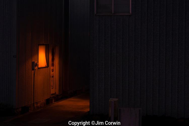 Door illuminated by a lamp along alleyway
