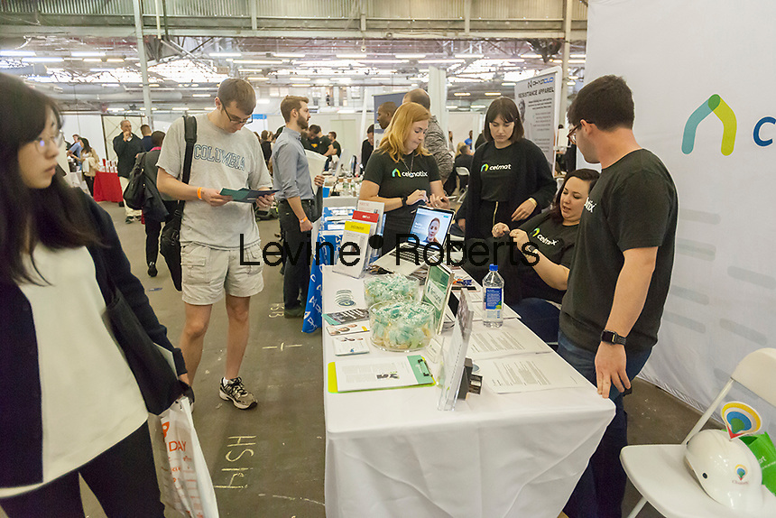 Workers from Celmatix speak to attendees at the TechDay New York event on Tuesday, April 18, 2017. Thousands attended to seek jobs with the startups and to network with their peers. TechDay bills itself as the U.S.'s largest startup event with over 500 exhibitors. (© Richard B. Levine)