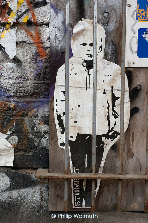 Cut-out print of a boy behind a security grill on a boarded up shop in Shoredich, London.