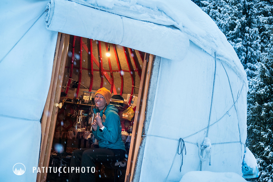 A woman skier sits inside a backcountry yurt while on a ski touring trip in the Aksuu Valley of Kyrgyzstan