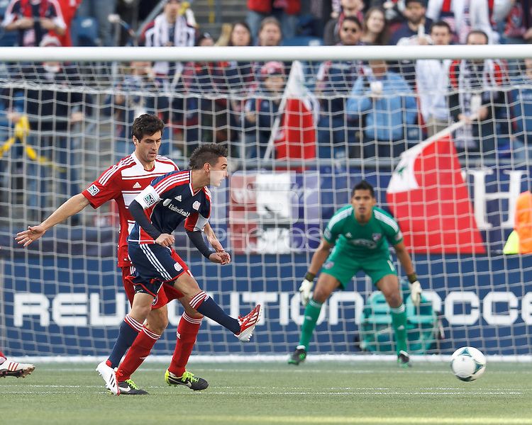 New England Revolution forward Diego Fagundez (14) passes the ball as FC Dallas defender George John (14) defends..  In a Major League Soccer (MLS) match, FC Dallas (red) defeated the New England Revolution (blue), 1-0, at Gillette Stadium on March 30, 2013.